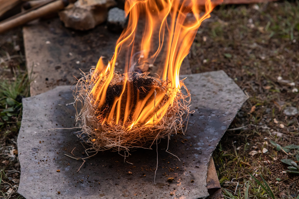 Flame,Burning,Using,Straw,As,Fire,Starter,On,Grey,Slate