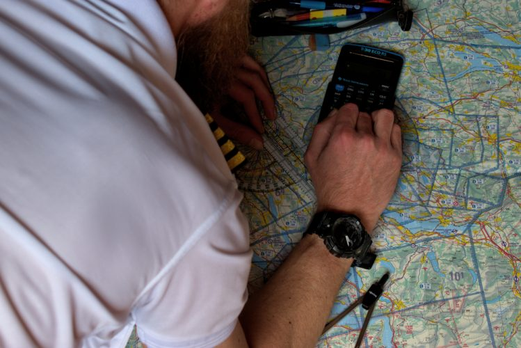 pilot is calculating his navigation route on an actual map